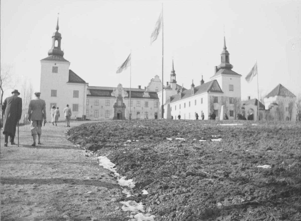 Menn og kvinner på vei opp mot Tyresö Slott. Slottet har tre etasjer og to gavletårn med kopperspir og ble på 1800-tallet tilbakeført til et barokkslott etter endringer og vandaliseringer de siste hundreårene. Vi ser rester av snø i veigrøften og vind i flaggene.