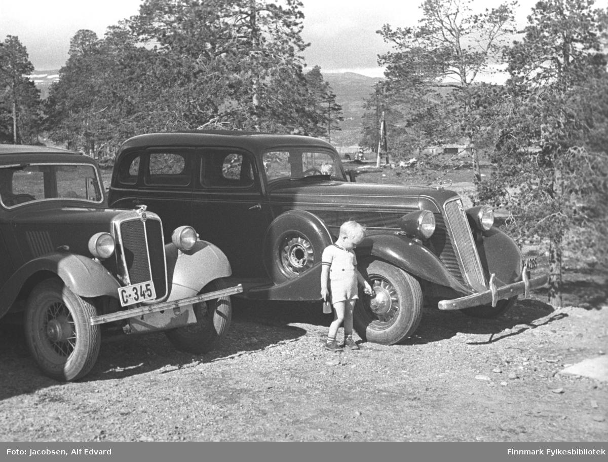 En sommerkledt Arne Jacobsen ser på biler som står  parkert i nærheten av NNHs gjestgiveri. Gutten har en lys t-skjorte med mørke striper i halsen og på ermene. Skoene hans er ganske mørke, sokkene er lyse med mørke striper og han har en lys shorts på seg. Han holder en liten lekespade i høyre hånd og venstre holder han mot hjulkapselen på forhjulet.  Bilene fra venstre: Englesk Morris 8 X-4265 ca. 1934-35. Reg.nr. C-345. C for Akershus. Morris 8 ble produsert fra 1935 til 1948.  Amerikansk Studebaker firedørs sedan fra 1935  (to dører på hver side) med reservehjulet montert i forskjermen. Plassen de står på har grusdekke og det er ganske mye løvtrær i bakgrunnen. En ganske stor gress-slette ligger bak bilene. Et stort fjell ses i bakgrunnen med noen snøflekker på toppene.