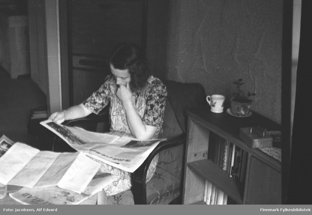 Aase Jacobsen sitter i en lenestol med avisa i fanget. Hun er iført en kortermet kjole med mye mønster. Lenestolen hun sitter i har mørklakkerte armlener og et forholdsvis lyst trekk som har litt mønster. En mørk jakke henger over stolryggen. På det runde bordet som står foran henne ligger flere aviser og noe papir. Ved siden av henne står en mørk bokhylle. En hvit kopp står oppå og ved siden av den står en liten potteplante. Et skrin eller eske ligger på den hvite, heklede duken. Begge hyllene i bokhylla er full av bøker og rommet lengst nede til høyre har en dør. Tapetet på veggen bak henne har mønsterog lengre mot venstre ses en døråpning. Helt til venstre står noe som muligens er et lyst skap eller hylle.