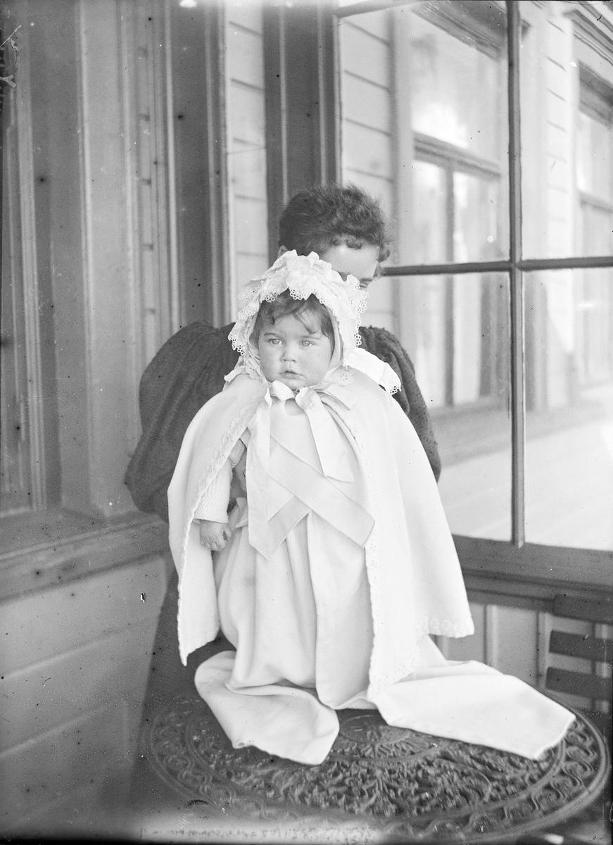 En kvinne holder et lite barn foran seg slik at det ser ut som barnet står på et bord. Barnet er kledd i cape. De er fotografert ute på en innglasset veranda.