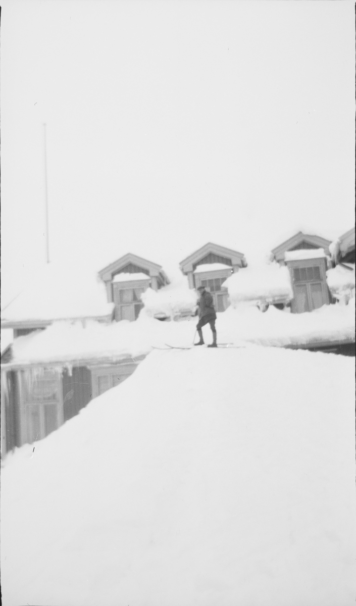 Mann på ski står nesten oppe på taket av Haugastøl stasjon og turisthotel.