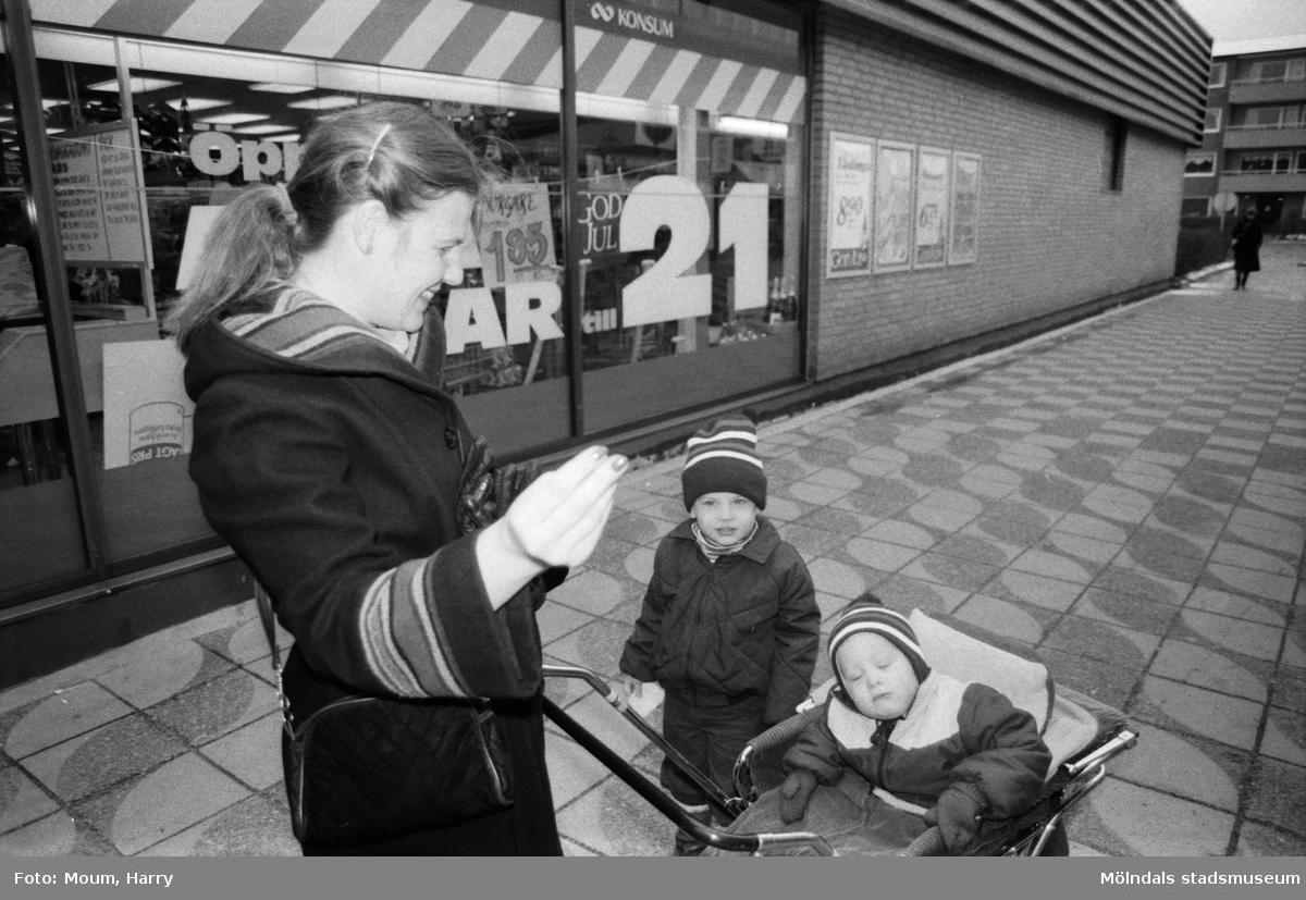 """Åsa Wahlberg med sönerna Christer och Johan i Kållereds centrum, år 1983.  """"Vad tycks? Vi frågade i Kållered centrum var de brukade göra sina inköp.  Åsa Wahlberg med barnen Christer och Johan möter vi på inre torget i Kållered. – Jag arbetar på B&W och tycker att det är mycket billigt och bra att handla där. Å andra sidan bor jag i Kållered och tycker det är bekvämt att handla en del av dagligvarorna här, och ibland hittar jag faktiskt matvaror till ett billigare pris här på torget.""""  Fotografi taget av Harry Moum, HUM, för publicering till enkäten """"Vad tycks"""" i Mölndals-Posten, vecka 49, år 1983."""
