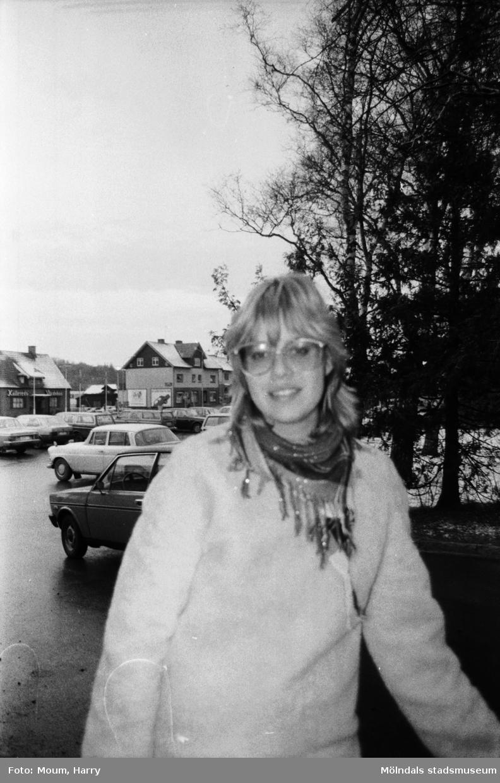 """Yvonne Gustavsson i Kållereds centrum, år 1983.  """"Vad tycks? Vi frågade i Kållered centrum var de brukade göra sina inköp.  Yvonne Gustavsson frågar vi medan vi står och fryser i snålblåsten. Det är ju vintertid. – Jag handlar faktiskt det mesta här i Kållered. Det kanske inte är billigast här, men jag både arbetar och bor i Kållered, så det är bekvämt och avstressande att handla här.""""  Fotografi taget av Harry Moum, HUM, för publicering till enkäten """"Vad tycks"""" i Mölndals-Posten, vecka 49, år 1983."""