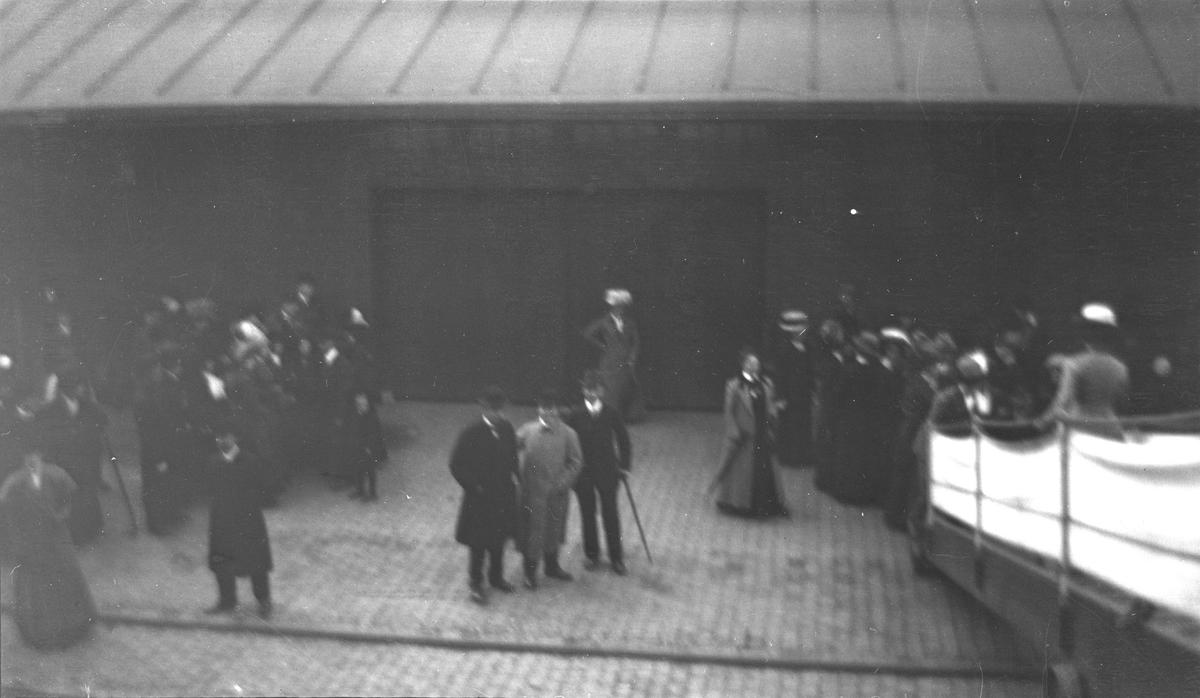 Fotografi fra en kai i forbindelse med en reise. En gruppe bestående av menn og kvinner oppholder seg på kaien eller går opp og ned landgangen.