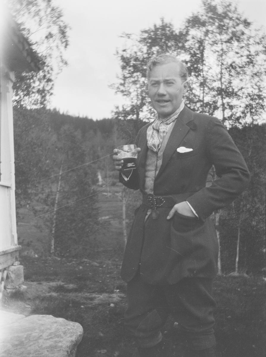 Iacob Ihlen Mathiesen står med et glass hånden utenfor familiens fritidsbolig i Jeppedalen. I bakgrunnen sees eng og skog.