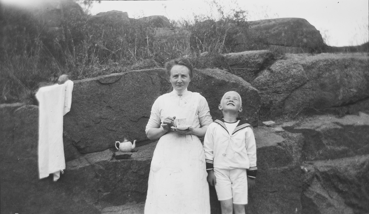 En kvinne og en Iacob Ihlen Mathiesen lener seg mot steinhyller og kvinnen holder en kopp med asjett under i hånden. Det står en tekanne på steinhyllen i bakgrunnen. En duk eller et håndkle henger også fra en berghylle bak de to.