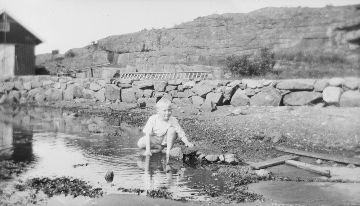 En gutt sitter på huk i strandkanten og myser mot sola og fotografen. I bakgrunnet sees en oppbygd vei og et bygg.