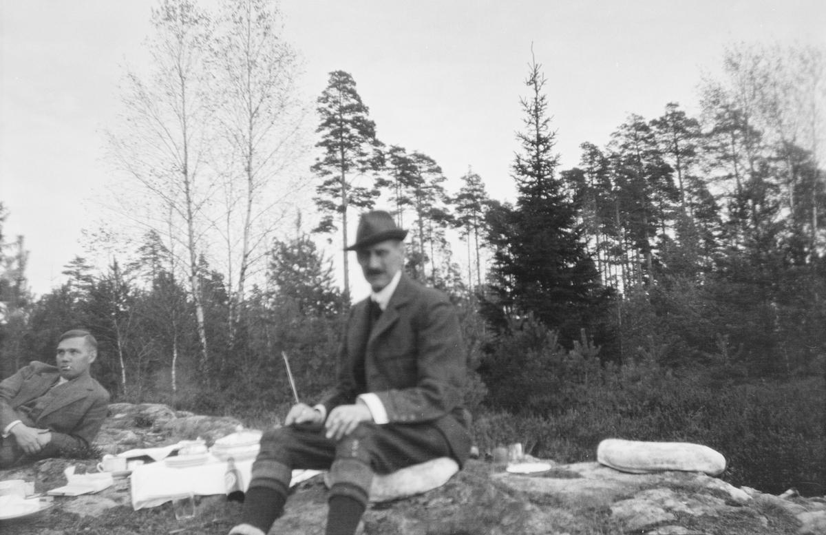 I front sitter en mann på en pute lagt direkte på bakken. En annen mann ligger hvilende på den ene albuen. Bekke er kledd i fritidsklær. Bak disse to er det blandingssskog.