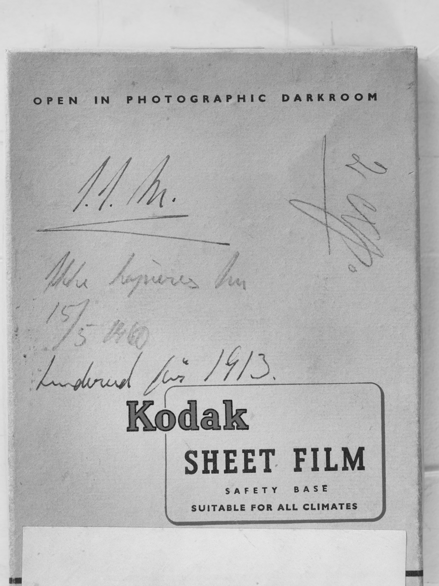 "7 glassplater lå i denne konvolutten hvor ""OPEN IN PHOTOGRAPHIC DARKROOM, KODAK, SHEET FILM, SAFETY BASE, SUITABLE FOR ALL CLIMATES"" er trykket på forsiden av konvolutten."