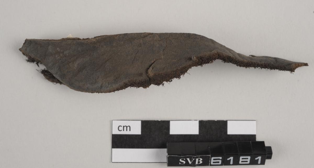 Avlangt og delvis bøyd lærfragment. Fragmentet har en brun farge og smalner fra den ene enden mot den andre.