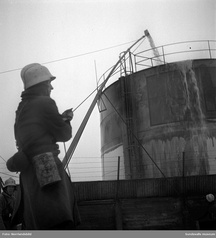 Oljebrand i en cistern vid Vindskärsvarv. Brandkåren släcker med skum.
