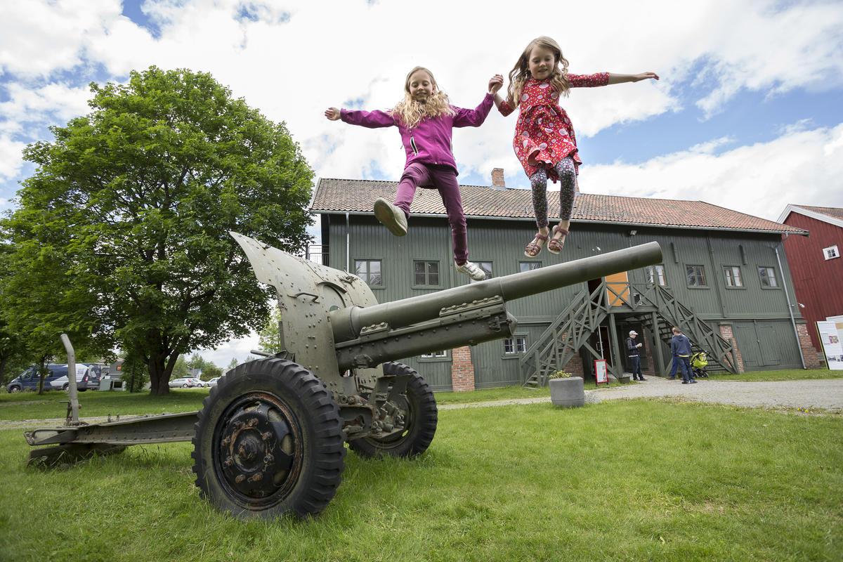 To jenter hopper ned fra en kanon som står utenfor hovedbygningen
