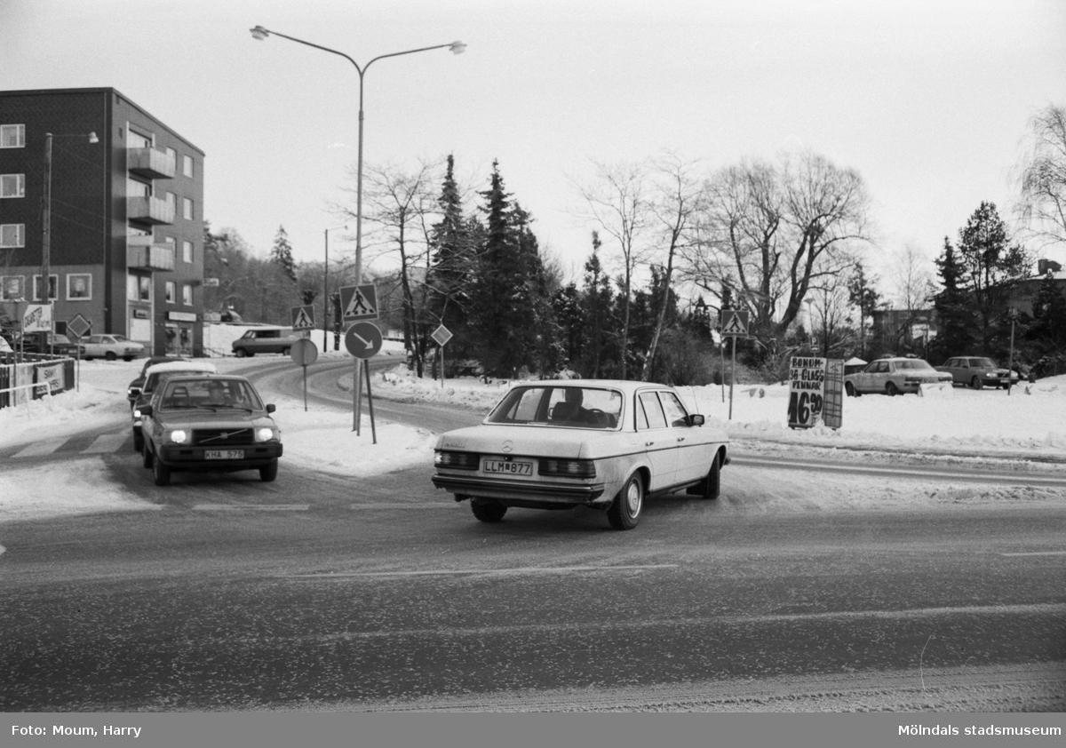 """Trafik i korsningen Gamla Riksvägen-Streteredsvägen i Kållered, år 1984.  Fotografi taget av Harry Moum, HUM, Mölndals-Posten, vecka 4, år 1984.  Bildtext: """"Trafik och parkering i Kållereds centrum är ett stort problem. Man måste hålla tungan rätt i munnen och titta åt alla håll. Säkert önskar många Kålleredsbor lite ordning i all oreda. Snart hoppas man komma gång med en utredning om trafiksituationen."""""""