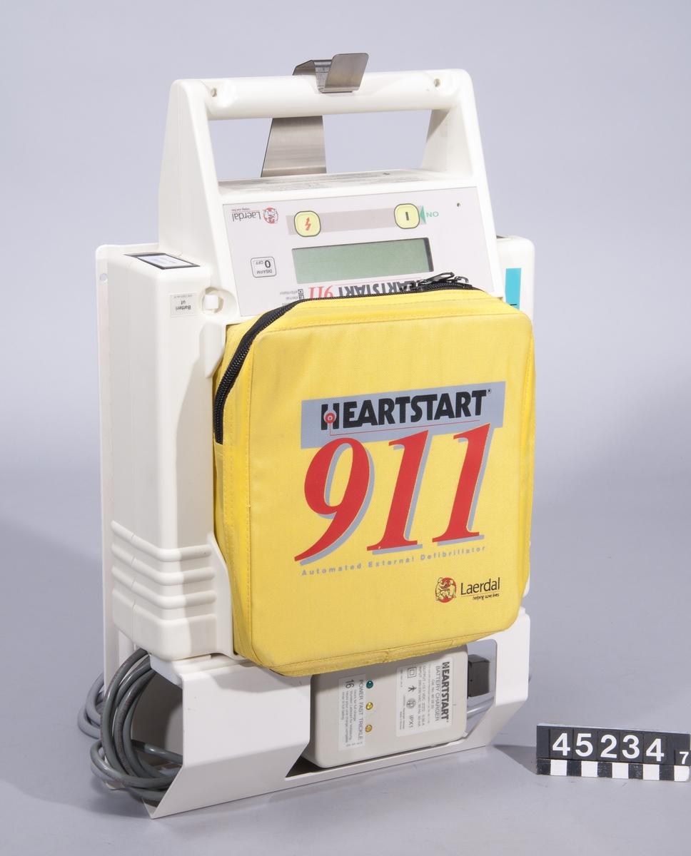 """Defibrillator för undersökning av hjärtrytm och vid behov defibrillation med påföljande stimulering av hjärtat.  Apparaten används enligt följande, förenklat: Patienten har förlorat medvetande, andning och puls. Självhäftande elektroder fästs på patientens bröstkorg, apparaten startas. Om utrustningen känner av att elektroderna är rätt fästa ger den efter ca 15 sekunder anvisning om att användaren ska trycka på knappen för """"analys"""". Användaren varnas också med ett röstmeddelande för att röra patienten under analysen. Om utrustningen detekterar en behandlingsbar arytmi laddas den upp och ger röstmeddelande om att knappen för en chock ska tryckas ner. Sedan ber utrustningen om analys igen. Cykeln upprepas om ingen puls registeras.  Apparatväskan är utrustad med följande tillbehör: plasthandskar, rakhyvel (Bic engångshyvel), torkdukar, våtservetter och en förpackning elektroder.  Med apparaten följer också en laddstation att montera på vägg, heartstart 911 charging rack, cat nr. 901940. Batteri cat nr. 901100 """"bäst före feb 2004"""". Cartridge för halvautomatisk drift, """"Medical control module plus"""" cat nr. 920100, ser nr. 36026."""