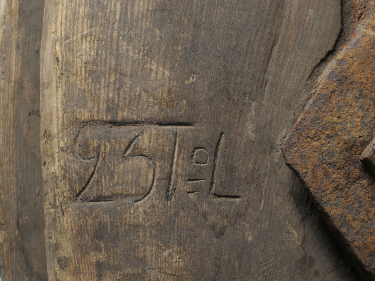 Blokk, enskivet. Innskåret F6, med pukkenholt  skive, svær jernkrok. Svær blokk, beslått med et langsgående jernbånd som ender i tykk kraftig krok. Midt på blokken er jernbeslaget ruteformet (DI: 20) med en stor bolt med ruteformet hode. Innskåret på siden:   C T 2 T.