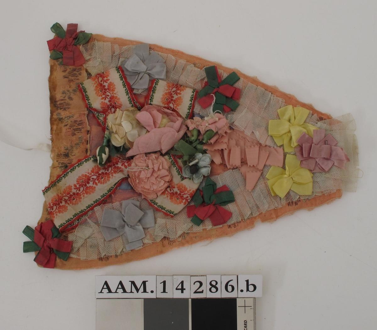 Brystduk, rosa silke, dekket av meget tynn lysblå silketyll,  over denne tett besatt med silkesløyfer i  lilla, rosa, gult, sterkt grønt/rødt, lyseblått.  Pm. hvitt/kirsebærfarget og grønt silkebånd i  kryss med hvite og rosa tvil tøyblomster.  Langs kanten rosa silkebrokadebånd, over dette  På langsidene et tyllbånd. Mellomlegg av gulhvitt  Ullstoff, på baks. gullig linstoff.