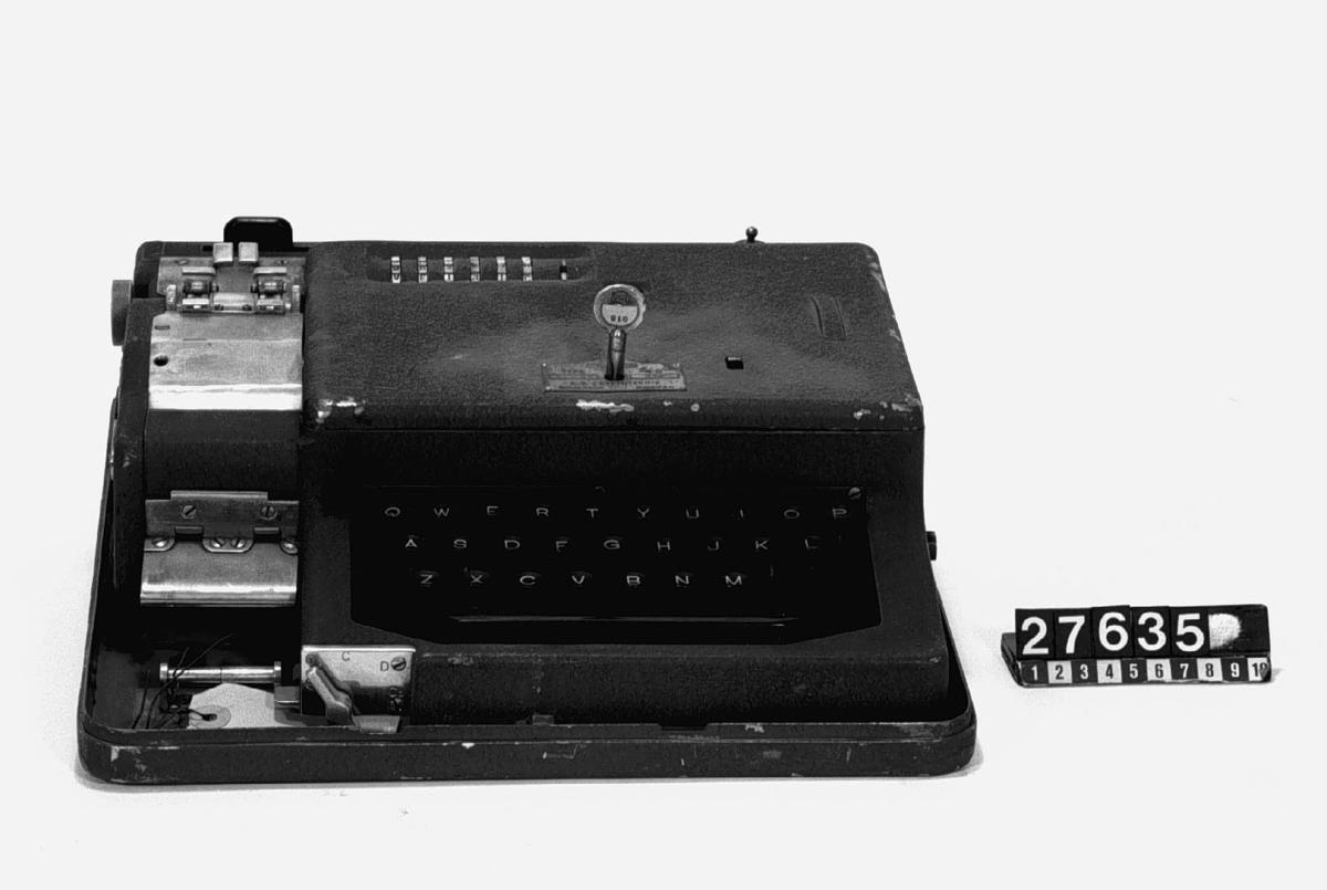 Mekanisk krypteringsmaskin med tangentbord och sex inställningshjul. Med skrivare för två pappersremsor, en kodad och en i klarskrift. Elektrisk drift, Nyckel till huven separat.