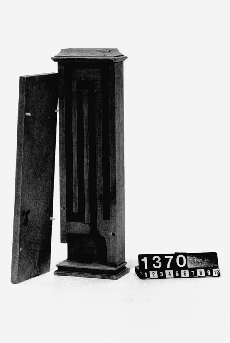 """Modell av kakelugn. Text på föremålet: """"N:o 145. Kakelugn .... Af Presid. Gref. Cronstedt. D.b.B.5 a-Tab.V"""". I Jonas Norbergs förteckning från 1779 beskrivs modellen på följande sätt: """"Modell på en platt kakelugn, som intet tager mycket rumm# har fin rökgång långt ner, innan den kommer i skorstenspipan."""""""