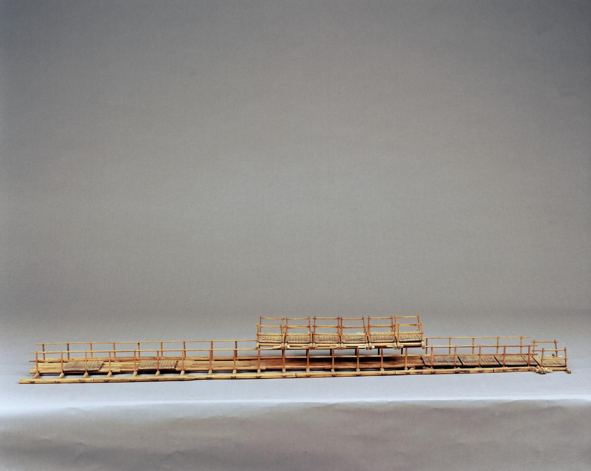 """Modell av flottbro. Trasig, sektioner har lossnat. Text på föremålet: """"D.2. XVI (?) """" Etikett oläslig. I Jonas Norbergs förteckning från 1779 beskrivs modellen på följande sätt: """"Modell på Flottbro, med paraboliske flytande bågar på bägge sidorna, bygd vid några ställen öfver Dahlälfven, och beskrefven i Kongl. Vet. Academiens Handlingar, för år 1743, första Qvartalet."""""""