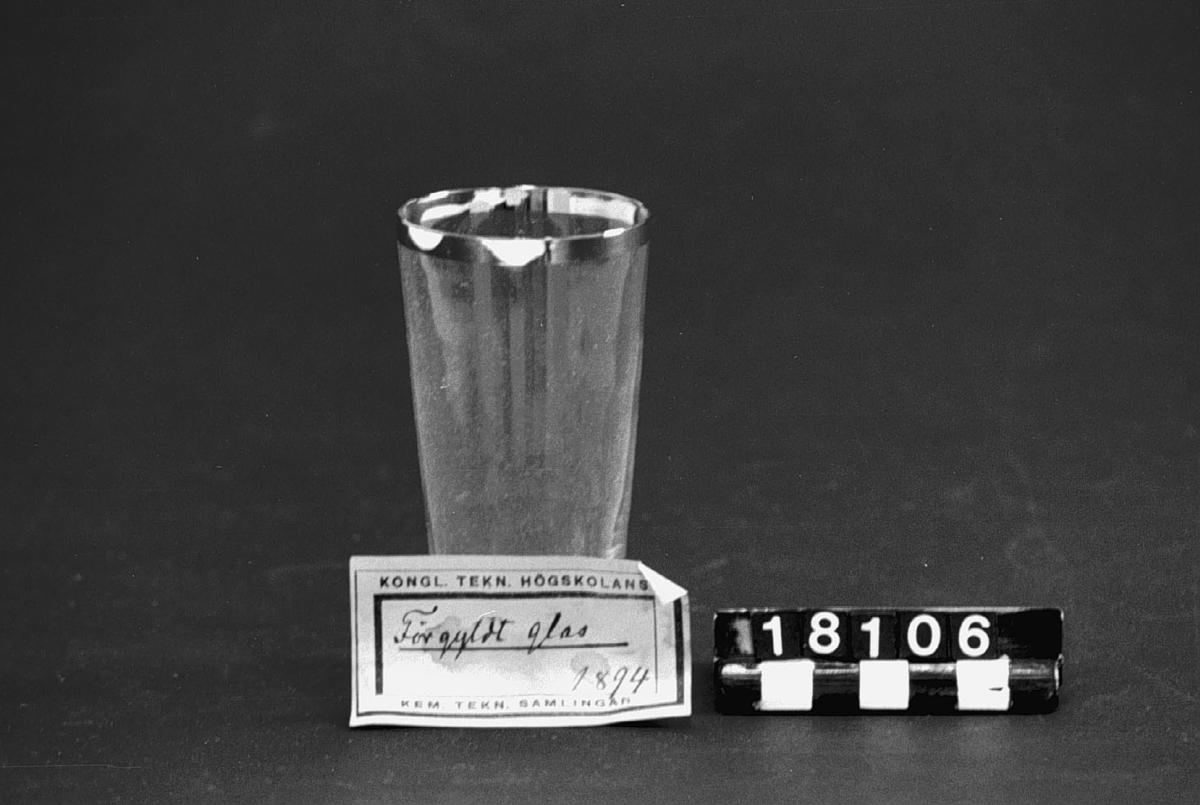 """Glas med förgylld kant, utan fot. Etikett: """"Förgyldt glas 1894""""."""