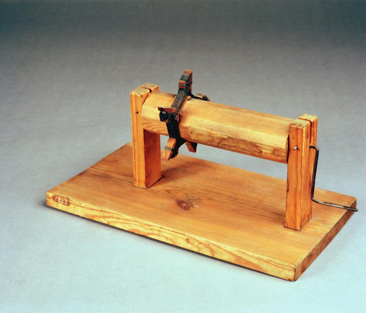 """Modell av hjulstock med lyftarmsring av tackjärn. Text på föremålet: """"N:o 203. Modell på gutna Tackjerns lyftarmar. Efter Kongl. Wett: ac: Handl. 4de Q: 1774. V.B.3""""."""