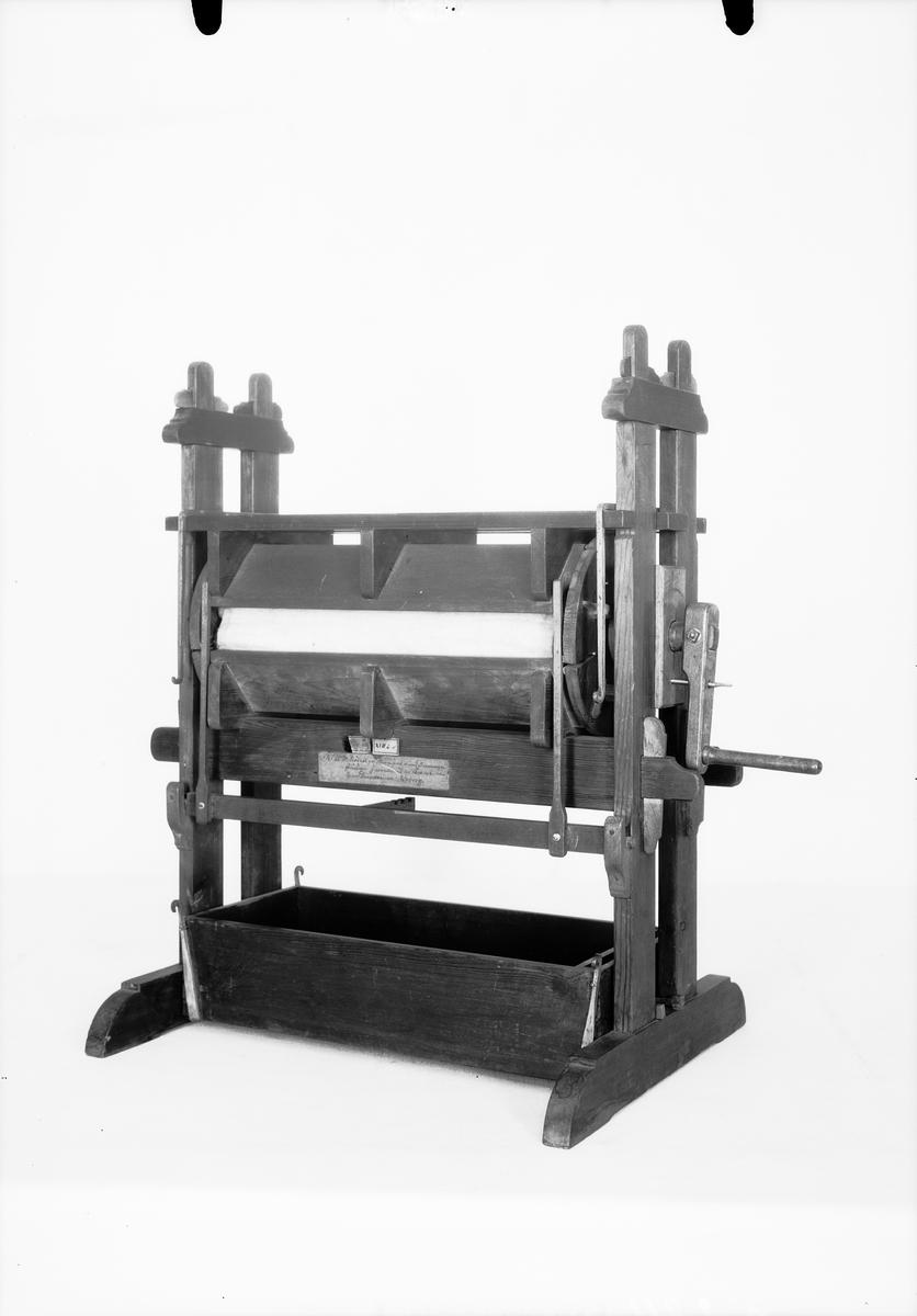 "Modell av mangel. Text på föremålet: ""N:o 207. Modell på Mangel med 5 mangelståckar. Inventerad af Framledne Herr Directeuren Norberg. C-e-13 XVII.E.11. N:o 9""."