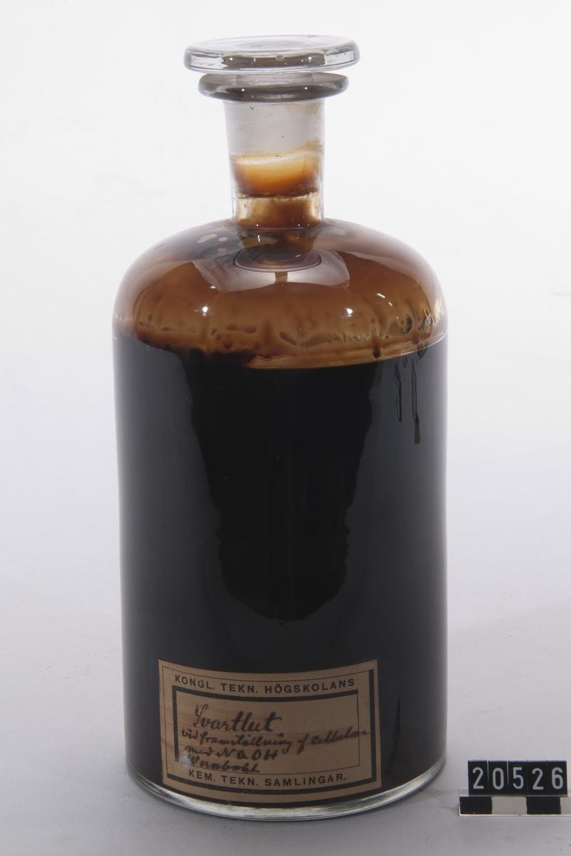 """Prov på svartlut. I flaska av glas med etikett: """"Svartlut vid framställning av cellulosa med NaOH, Wernbohl""""."""