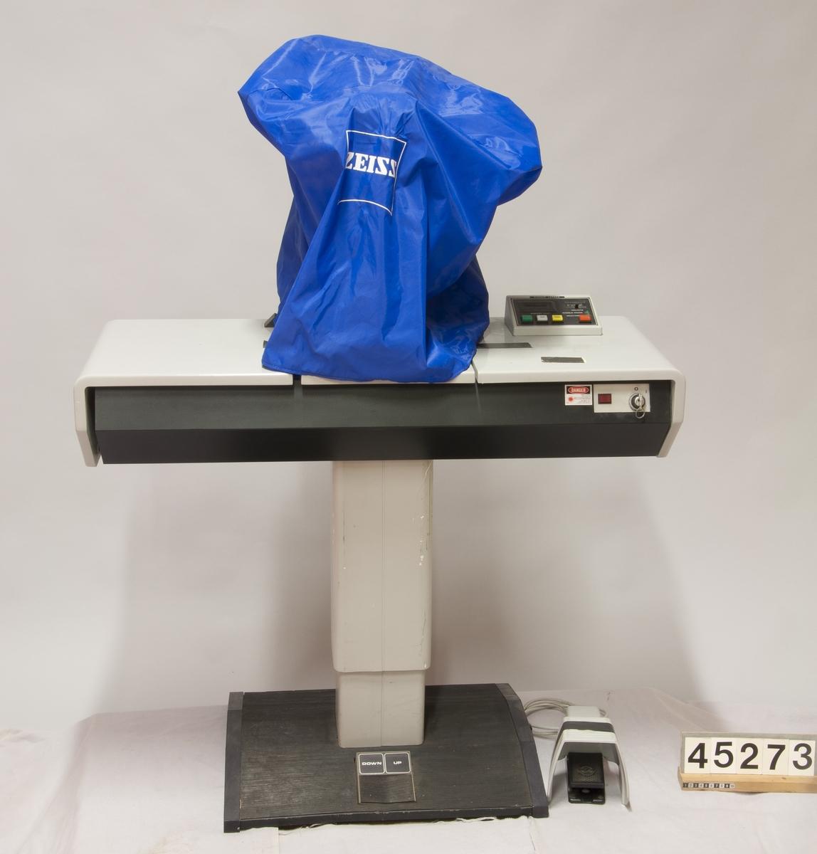 """Q-switchad YAG-laser med våglängden 1064 nanometer (infraröd). Effekt per puls några få millijoule. Fokusering görs med HeNe-laser. Laserhuvudet är vattenkylt, strömförsörjning och kylvattenpump är integrerade i bordet.  En YAG-laser används för behandling av efterstarr efter att linsen i ögat bytts ut mot en konstgjord. Man kan behöva """"klippa"""" bort delar av linskapseln som grumlats. Den kan också användas för att klippa hål i regnbågshinnan (iris) vid trångvinkelglaukom eller klippa av strängar och grumlingar djupare in i ögat.  Till utrustningen hör: - två mikroskopobjektiv f=125 mm samt två okular 2,5 x. - fyra kontaktlinser för behandling varav: - två linser CGA 1 för behandling i kammarvinkel, tillverkare Lasag AG, Thun, Schweiz - en lins CGP 1 för behandling i pupillregionen, tillverkare Lasag AG, Thun, Schweiz - en lins """"Osmy trokel single mirror"""" tillverkare Ocular Instruments, Inc. Bellevue, Wa, USA - en pedal för att aktivera lasern, typ F1 SU1 tillverkare Bernstein Schaltsysteme, Porta, Westfalen, Tyskland - skyddshuva i nylon märkt Zeiss  Behandlingen går till så att läkaren ser in i ögat genom utrustningens mikroskop. Till hjälp för fokusering av lasern finns synligt laserljus. En kort puls av laser med högre effekt fokuseras i vävnaden, där en ångblåsa omedelbart bildas och spränger isär vävnaden. Genom att upprepade gånger """"klippa"""" i ett grumlat område av linssäcken skapas en öppning så att ljus åter kommer obehindrat genom ögat."""