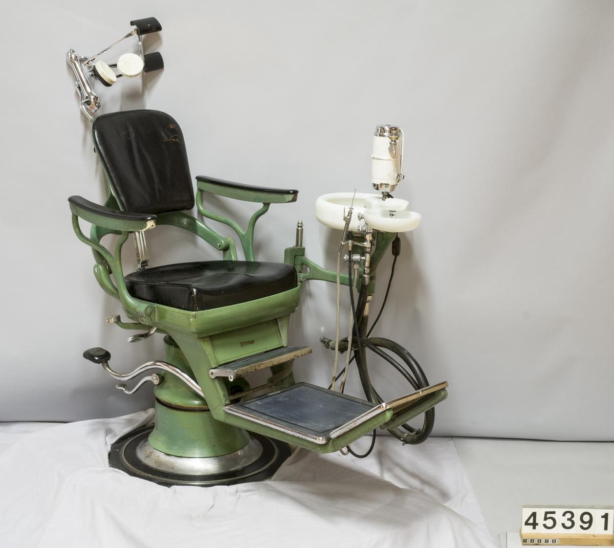 Behandlingsstol med ställbart nackstöd och fotstöd. Sits av läder, armstöd av syntematerial, gummibelagt fotstöd. Armstöd för tandläkaren. Stolen är höj och sänkbar med hjälp av pedaler. På en arm sitter en sköljkopp i glasmaterial för anslutning till vattenledningssystem. Lackerad i en grön nyans som var typisk för denna tillverkare.