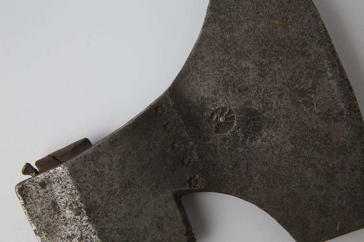 Stridsøks med fem stjerner innslått på overgang mellom hammer og blad. På høyre side innslått avvikende skjellformet smedmerke. Øksen har gammelt skaft, med gjennomgående skinner på overside og underside. Skinnen på undersiden har et brudd ca. 2 cm fra skafthullet. Skaftet har svidekor og doppsko der piggen mangler.