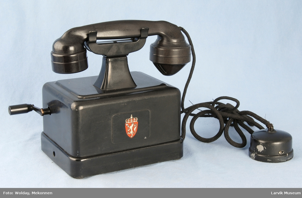 Form: Kvadratisk kasse med holder for telefonrør på topp, sveiv på siden.