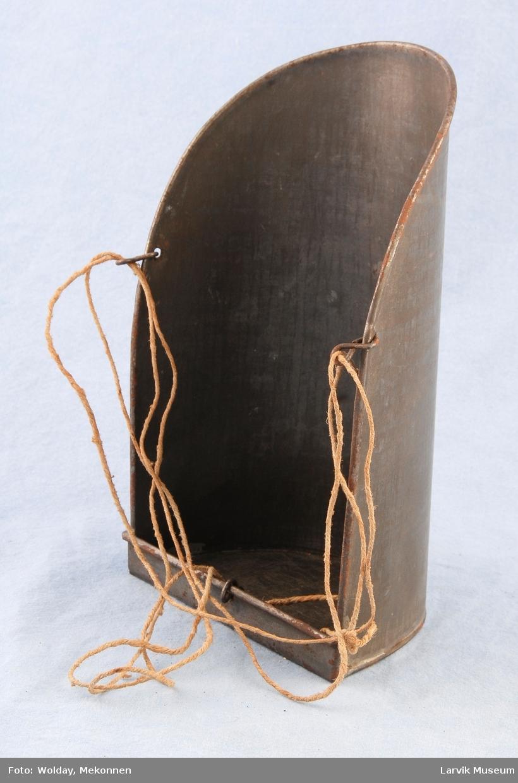 """Teknikk: valset jernplate tilkuttet, bøyd i halv- sirkel, kantene brettet dobbelt. tilbøyd ende loddet på. 3 """"8 talls""""-bøyler festet i hull i kantene på platene.hyssingen festet til disse. Form: tilnærmet skuffeform, platen er buet i forhold til den halvsirkelformede enden hvis radius står vertikalt på den buede platen. den andre enden på """"skuffen"""" er """"jevnt avbuet"""". den halvsirkelformede endens kanter er loddet utenpå platen."""