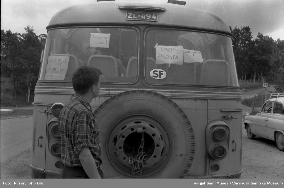 Oleif Nilsen Elen kikker på plakater i bakvinduet på en finsk buss som står på en parkeringsplass. Ukjent sted høst 1966.