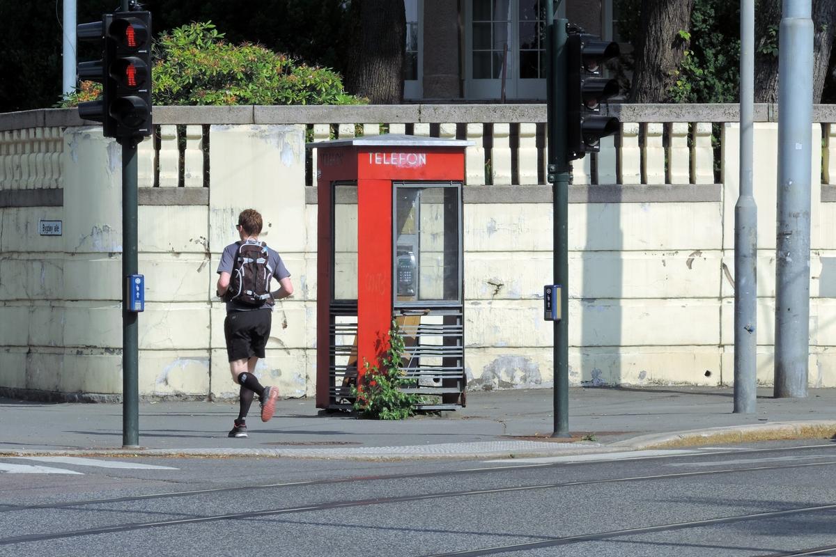 Telefonkiosken står på Olav Kyrres plass 1 ved den polske ambassade. De røde telefonkioskene ble laget av hovedverkstedet til Telenor (Telegrafverket, Televerket) Målene er så å si uforandret.  Vi har dessverre ikke hatt kapasitet til å gjøre grundige mål av hver enkelt kiosk som er vernet.  Blant annet er vekten og høyden på døra endret fra tegningene til hovedverkstedet fra 1933. Målene fra 1933 var: Høyde 2500 mm + sokkel på ca 70 mm Grunnflate 1000x1000 mm. Vekt 850 kg. Mange av oss har minner knyttet til den lille røde bygningen. Historien om telefonkiosken er på mange måter historien om oss.  Derfor ble 100 av de røde telefonkioskene rundt om i landet vernet i 1997. Dette er en av dem.