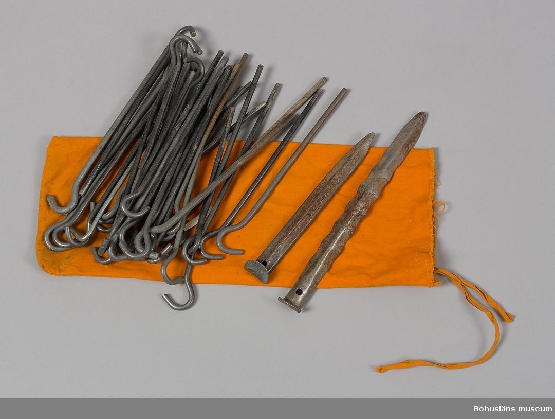 """Tältpinnar av rundstål, kromatbehandlade. Tältpinnarna (35 st samt två bockade metallstag av aluminiummed tandad kant) är förpackade i en liten säck med dragskosnörning av samma orange tältduk, på insidan med anteckning """"39"""", UM27670:4. Tältpinnarna hör till förgård UM27670:2.  Förgården hör till stativtält modell Malaga de lux 35197, UM27670:1.  Till förgården hör också tältstänger UM27670:3 samt vägledning för uppsättning och nedmontering UM27670:5."""