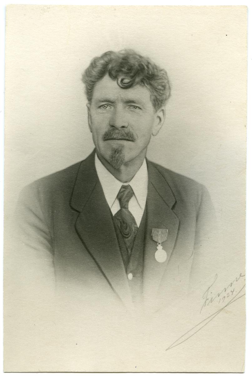 Portrett av mann i halvfigur. Mannen er iført skjorte med slips og en mørk dressjakke. På kragen har han en medalje.