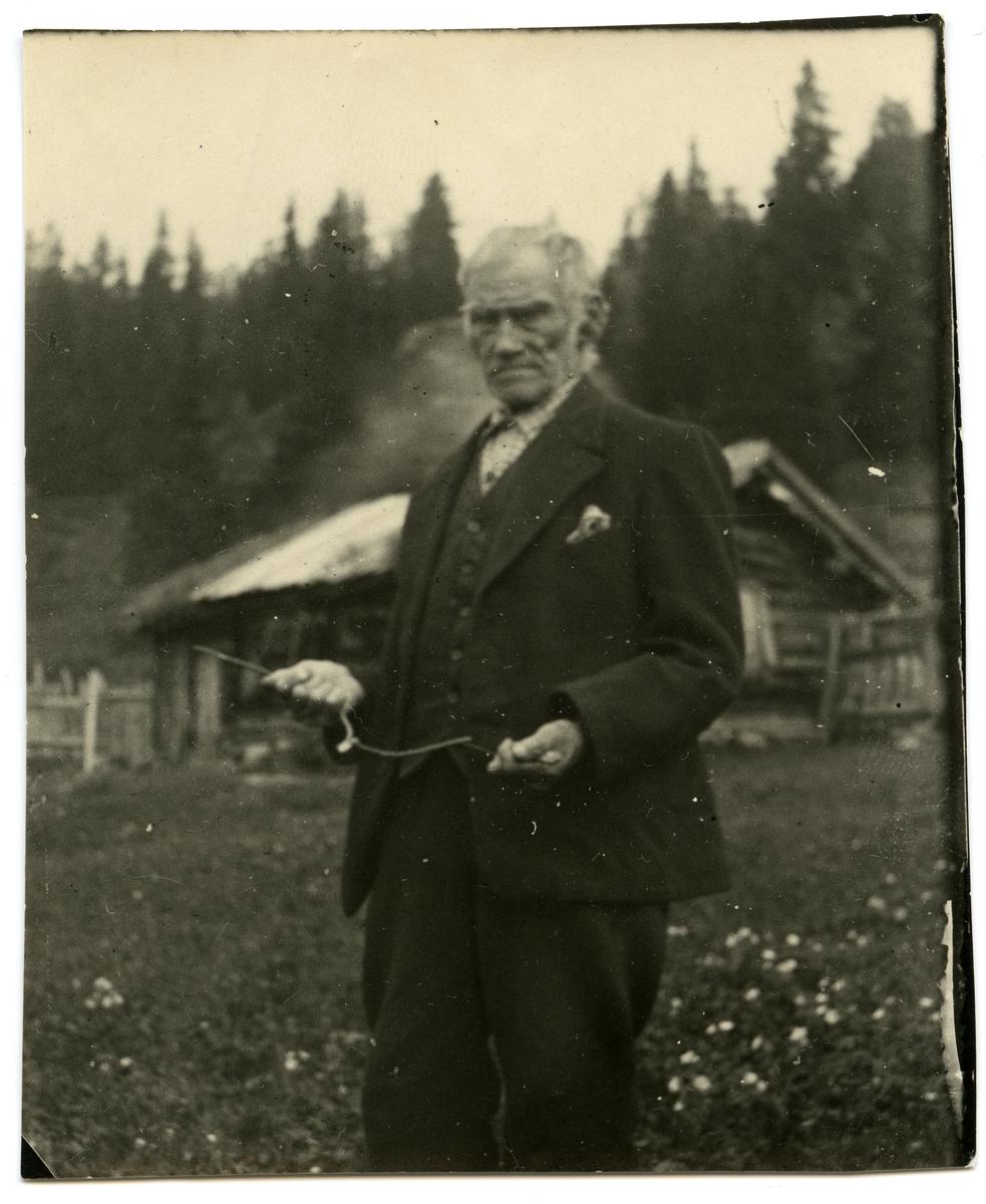 """En eldre mann ikledd dress står foran et gammelt trehus. I hendene holder mannen en såkalt """" ønskekvist """"."""