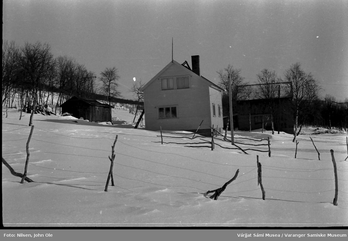 Vinterbilde av huset til Signe og John Ole Nilsen i Bunes. Vi ser vedskjulet, stabburet, huset og fjøset. 1967.