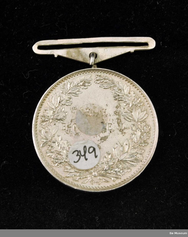 Sirkelformet medalje med feste for bånd