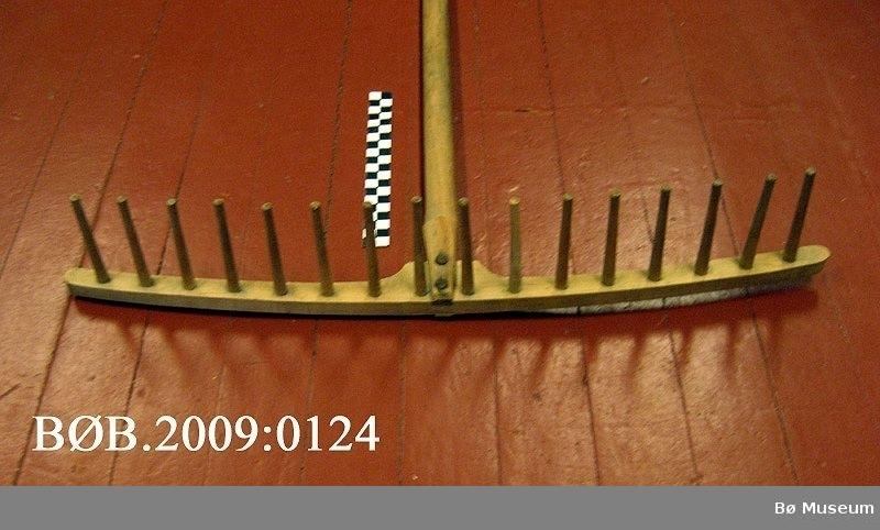 Trerive med 16 tretindar. Dreia riveskaft. Riveskaftet og rivehovudet er sett saman med metallnaglar. Nokre av rivene manglar nokre tindar.