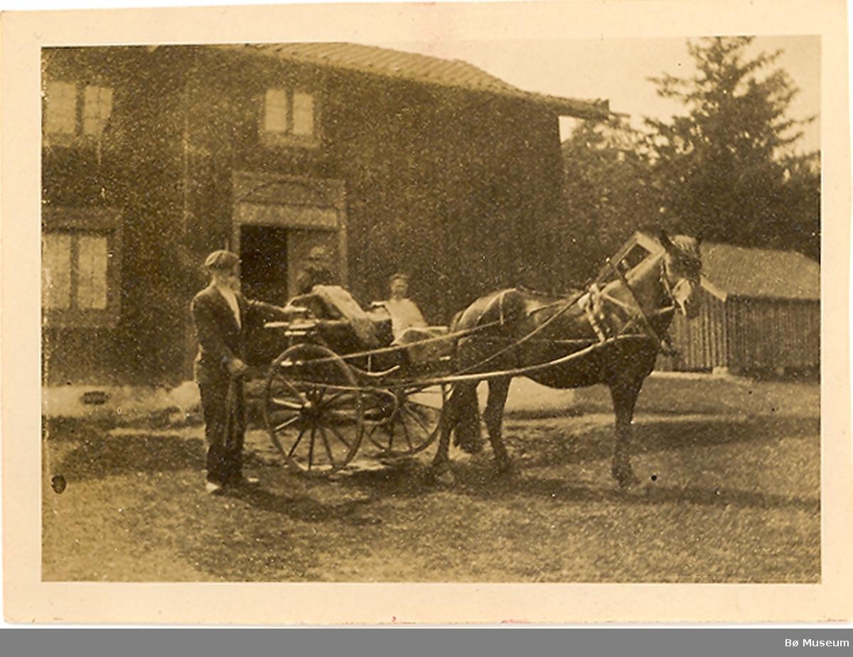 Foto 1923. Mann med hest og kjerre i gardstun.