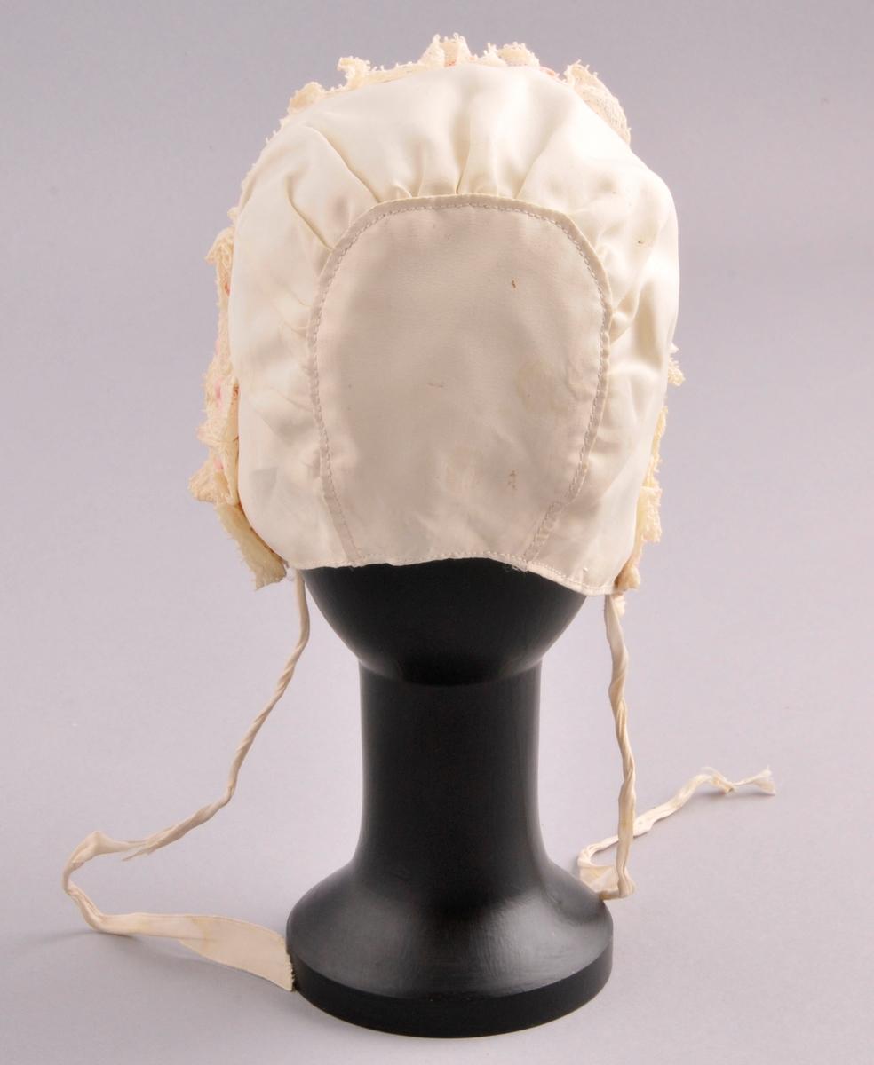 Luve av naturfarga bomull, med kjøpe blonde og silkeband rundt kanten framme. Luva er sauma saman av to delar. Luva har naturfarga for. Luva er sydd saman bak, ved at det er sett inn eit avrunda stoffstykke,med legg legg slik at luva får form. Luva har to knytebånd. Sydd saman med maskin.