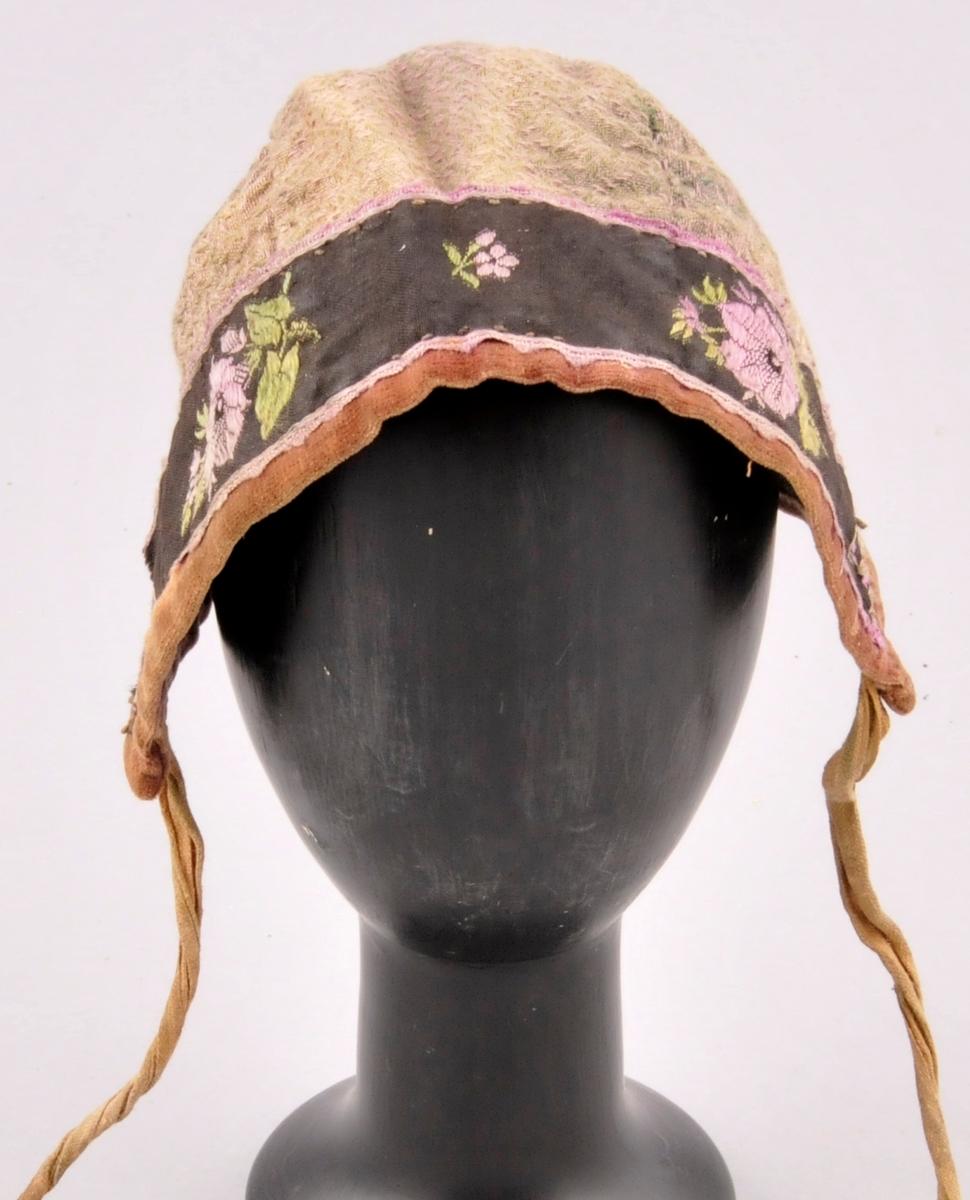 Luve av falma bomullstøy i lilla og grønblått. Eit blomstrete bommullsband langs opninga framme. Kanta med fløyel. For av rutete bomullslerret. To stripete bomullsband til å knyte luva fasst med. Luva er sydd saman av 3 delar.