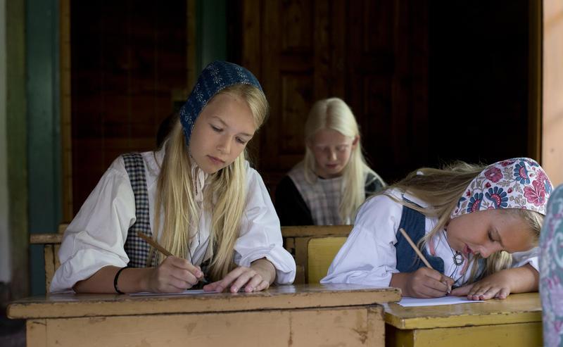 Tre piker i drakt ved gammeldagse skolepulter skriver