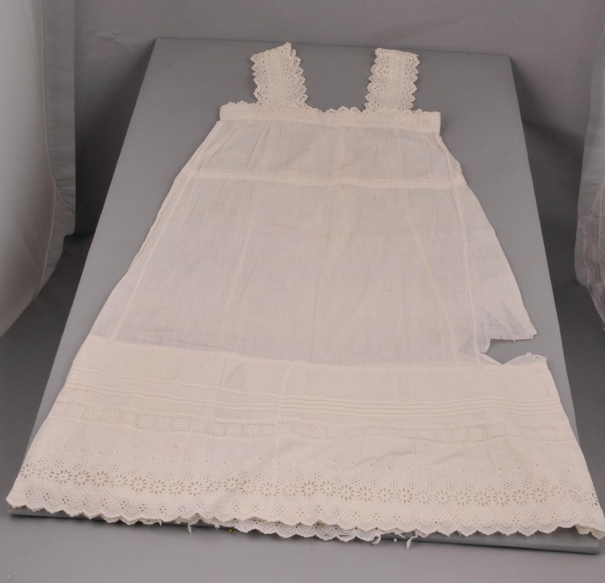 Kvit underkjole i tynnt bomullsstoff. Blonder og dobbelt stoff nede. To ulike typer blonder, fire små biser vannrett rundt heile kjolen.Selar av blonder øvst. Blondekant langs armhol og halsopning.Splitt i ryggen og snøring under brystet. Stofftrekte knappar og fire legg loddrett i ryggen. Loddrette saumar i sidene. Kjolen er sydd på maskin av kjøpestoff/kjøpeblonder. (Truleg er kjolen kjøpt ferdig).