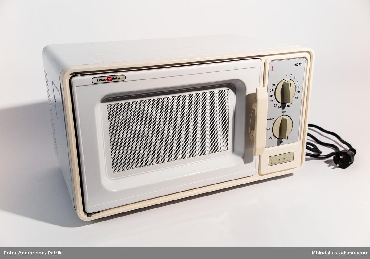 En mikrovågsugn (mikro) är en köksmaskin som värmer mat genom ett högfrekvent elektromagnetiskt fält. Detta åstadkoms genom att elektromagnetisk strålning genereras i mikrovågsugnen av en magnetron, vilket värmer vatten och andra polariserade molekyler i mat. En mikrovågsugn värmer mat snabbt men ger inte färg på samma sätt som konventionella ugnar. Detta gör att de är lämpliga för att återuppvärma samt tillaga vissa typer av mat. Denna helvita mikro är från 1980-talet och något sliten. Tillverkare är Elektro Helius och modellen är HC711. Stängningsluckan har ett galler ingjutet i glaset. Inne i mikron finns en fyrkantig glastallrik där man placerar det man vill värma. På utsidan finns två vridknappar där den översta är för minuter (1-30) och den nedersta med alternativen Medium, Defr., Låg och Min. Under dessa finns en start-knapp. På baksidan finns en etikett med produktuppgifter samt en svart, jordad kabel för svenska uttag.