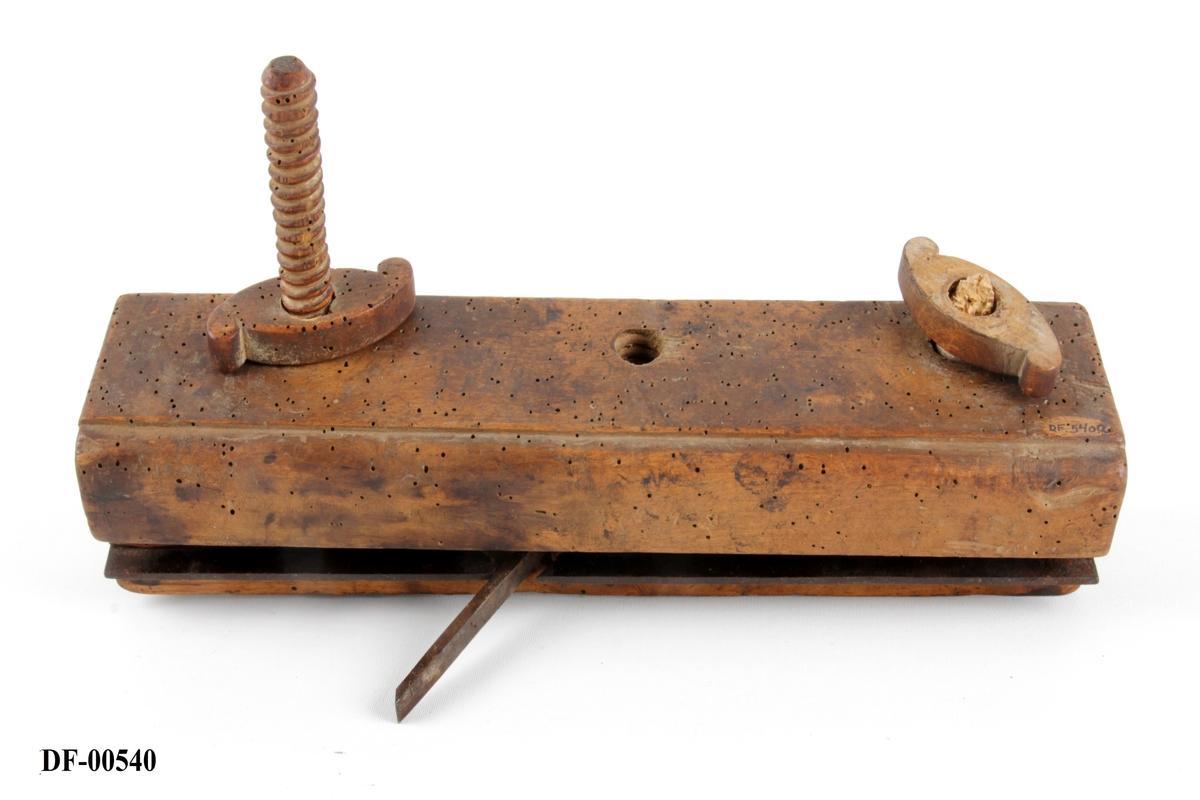 Nothøvel av tre, med jern langs banens midt (skinne).  Skinnen er innfelt i sålen. Skrudd fast på høvelen er en klemme bestående av en treplate og to gjengede treskruer med muttere. Regulerbar styrelist.