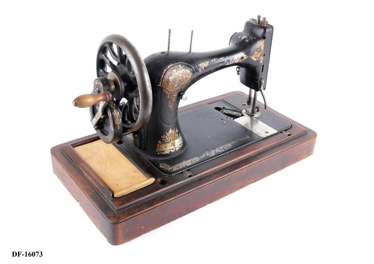 Symaskin på tresokkel. To spoler, spoleverk og håndsveiv. Snellerom integrert i tresokkelen. Gulldekor.