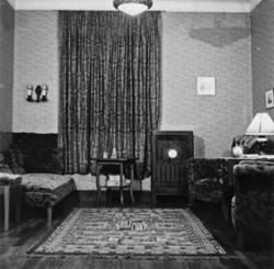 """Del av vardagsrummet, med """"dyscha"""", rökbord, radio och karam"""