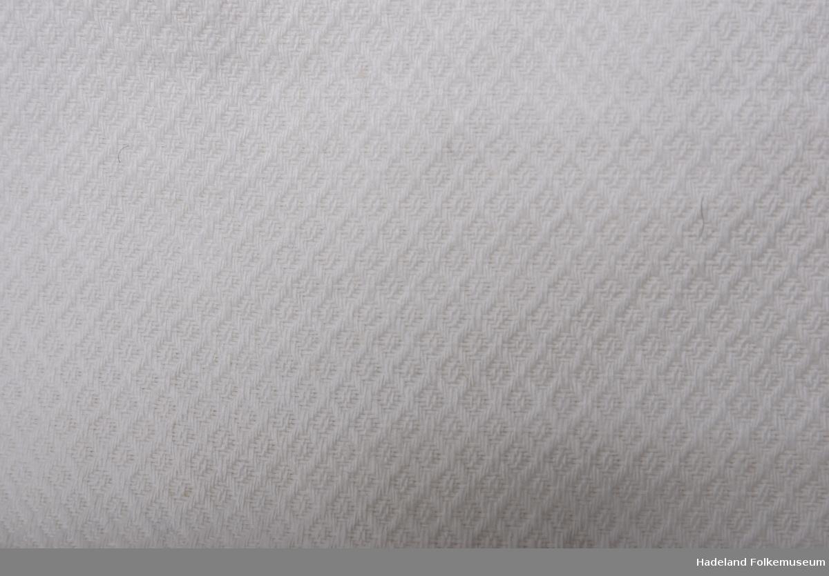 Spebarnstrøye.  Hvitt mønsterved bomullstøy med floss på vrangen. Kimonofasong med bendelbåndskanting. Lukning bak med 2 par bånd.